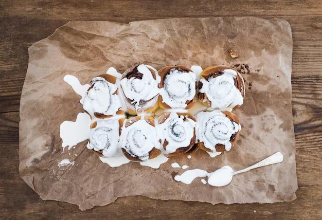 シナモンロール、素朴な木製の上の油性クラフト紙にクリームチーズのアイシング Premium写真