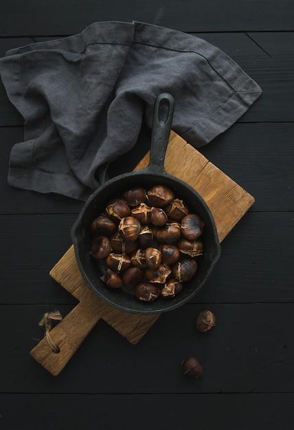 Жареные каштаны в сковороде железа на деревенском деревянной доске над черной таблицей, вид сверху. Premium Фотографии