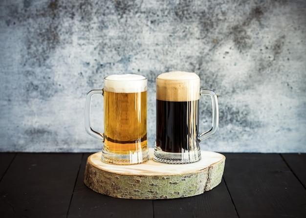 木の板にマグカップで明るいビールと暗いビール Premium写真