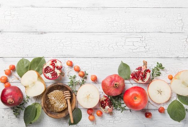 Рош ха-шана - концепция еврейского новогоднего праздника. традиционные символы: медовая банка и свежие яблоки с гранатом и рогом шофара Premium Фотографии