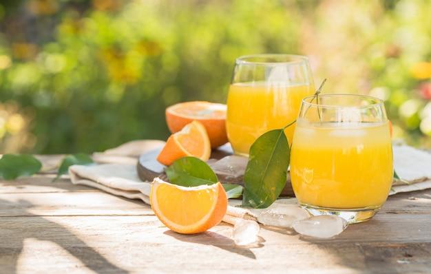 新鮮なオレンジジュース、熟したオレンジフルーツ、自然のスライスのガラス。新鮮なオレンジジュース、ストロー、オレンジフルーツ、オレンジスライスを絞った。 Premium写真