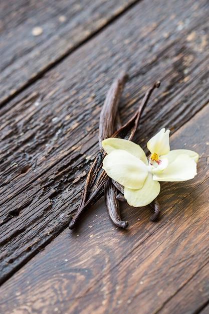 乾燥バニラスティックと木製のテーブルにバニラ蘭。閉じる。 Premium写真