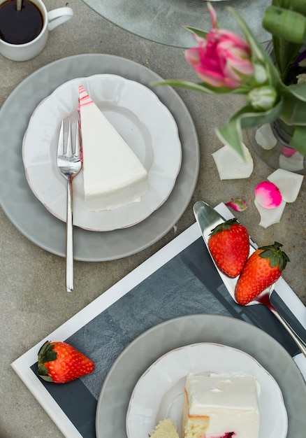 チューリップの花とイチゴのケーキデザートのスライス。 Premium写真