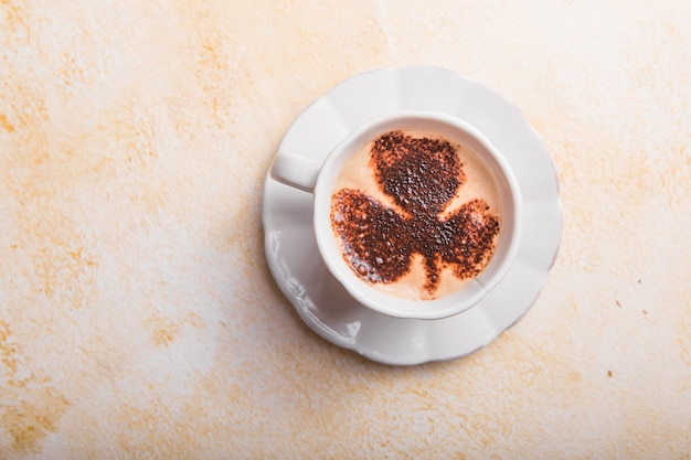 四つ葉のクローバーラテアートとコーヒーカップ Premium写真