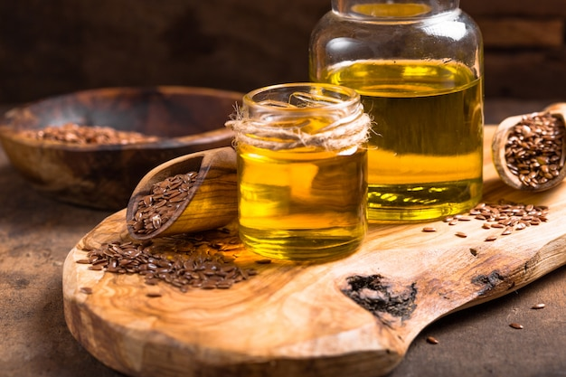 Семена льна масло и сырые семена на деревянный стол. Premium Фотографии