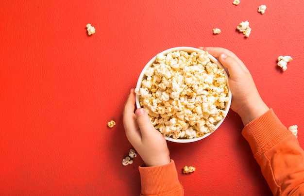 Свежий попкорн вылился из миски на красный Premium Фотографии