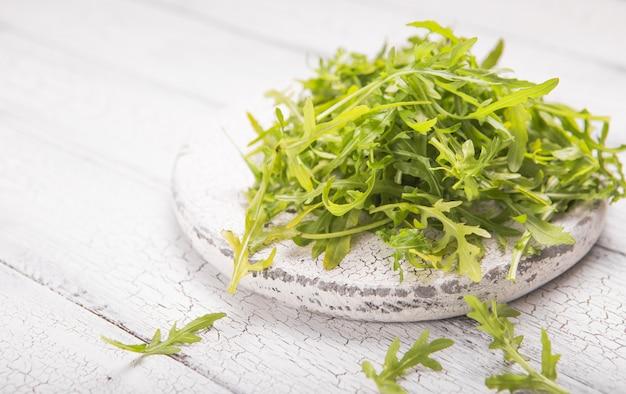 ホワイトボードに新鮮なルッコラの葉、テキストのための場所で素朴な木製の背景にルッコラロケットサラダ。セレクティブフォーカス、健康食品、ダイエット。栄養の概念 Premium写真