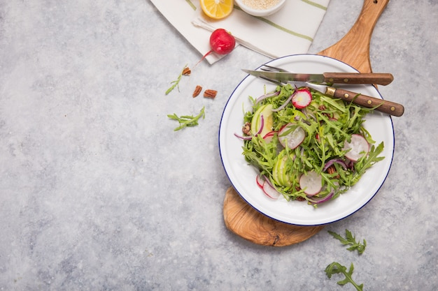新鮮な緑のルッコラは白いボウル、リンゴ、大根、ピーカンナッツ、タマネギのテキストと木製の素朴な背景にタマネギのルッコラロケットサラダに葉します。トップビュー、健康食品、ダイエット。栄養の概念 Premium写真