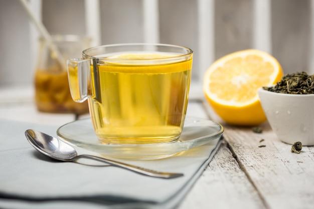 Чай в стеклянной чашке с листьями мяты сушеный чай нарезанный лимоном. Premium Фотографии