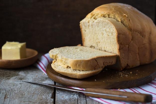 Свежий домашний хрустящий хлеб на деревянной стене. французский хлеб на закваске. пресный Premium Фотографии