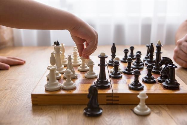 Папа и сын играют в шахматы вместе дома Premium Фотографии