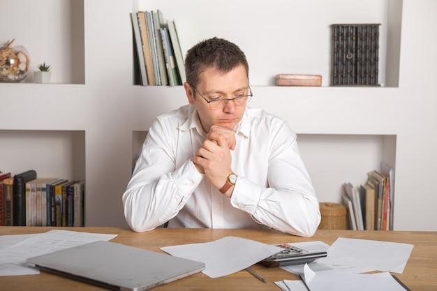 Молодой бизнесмен на рабочем месте с удивлением и шокирован выражением лица Premium Фотографии