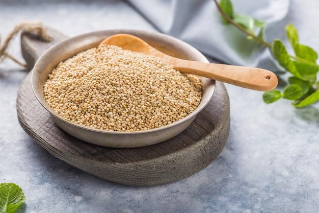 Сырые белые семена квиноа на тарелку с деревянной ложкой Premium Фотографии