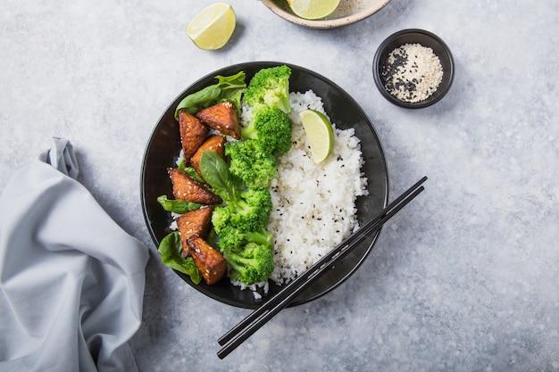 Веганские теряки темпе или темпе будда чаша с рисом, брокколи на пару, шпинат и лайм на сером фоне. здоровая пища Premium Фотографии