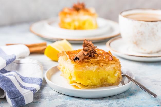 Заварной крем «галактобуреко» или бугатса, традиционный греческий десерт, запекается на сковороде с сиропом. Premium Фотографии