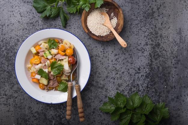 Салат нисуаз с тунцом, яблоком, помидорами черри и кунжутом на темно-серой поверхности. французская кухня. , Premium Фотографии