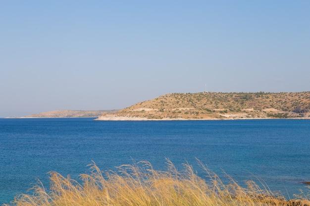 澄んだ青い水、金色の砂、カラフルなボート、山の美しいビーチの眺め。ギリシャとイオニア海の夏の風景。 Premium写真