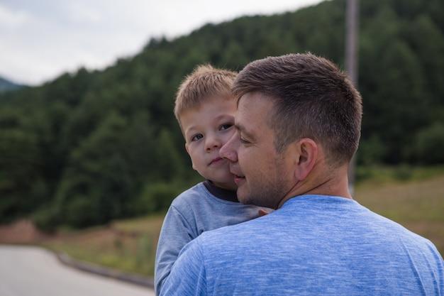家族のライフスタイルのパパと一緒に遊んで空気で幼い息子を保持している父 Premium写真