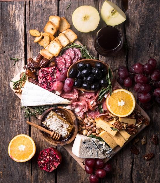 伝統的なイタリアの前菜プレート。木製のまな板に各種チーズ。ブリーチーズ、チェダースライス、ゴゴンゾーラ、クルミ、ブドウ、オリーブ、生ハム、ローズマリー、赤ワインのグラス。上面図 Premium写真