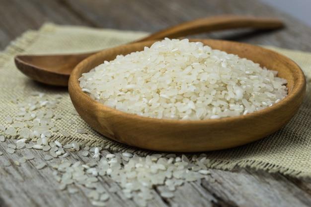 木のスプーンで磨かれた白いご飯。長粒米と丸粒米の背景。米柄米バスマティ米写真生米白米乾米。 Premium写真