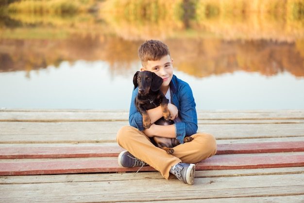 屋外の黒犬を抱き締める少年。友情、愛と関係の概念 Premium写真