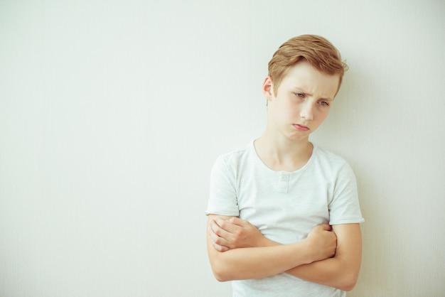 Разочарованный подросток мальчик стоит со скрещенными руками. копировать пространство Premium Фотографии