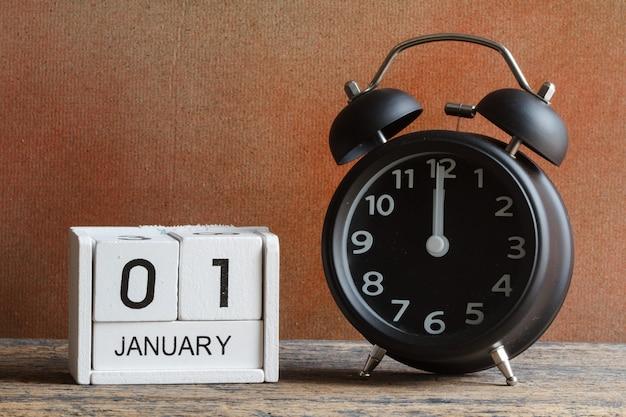 木製カレンダーと目覚まし時計で新年あけまして Premium写真