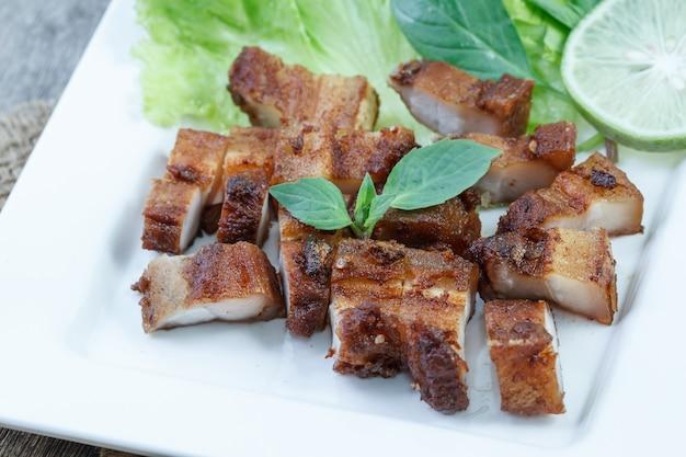 シャキッとした豚肉とニンニクとコショウの白いプレート Premium写真
