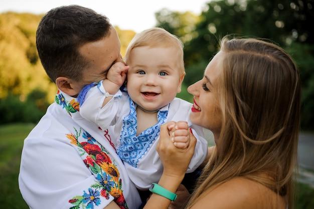 刺繍のシャツに身を包んだ笑顔の男の子を手に持って慎重な親 Premium写真