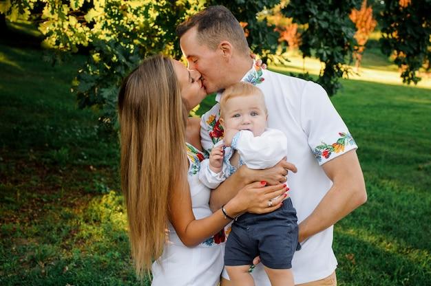 刺繍とキスに身を包んだ男の子を手に持って幸せな親 Premium写真