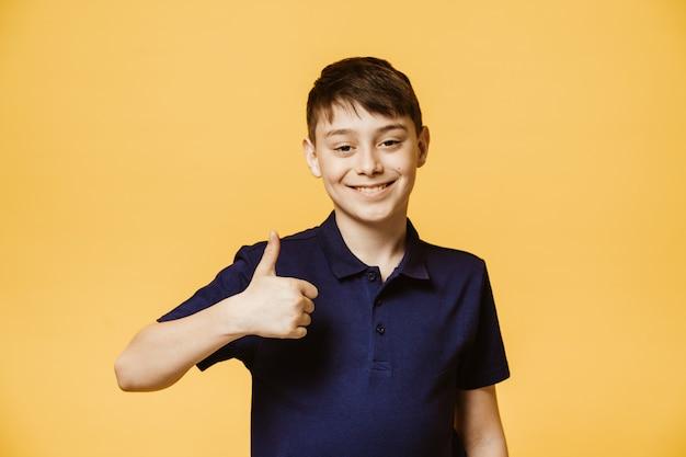 Позитивный кавказский мальчик показывает большой палец вверх знак, демонстрирует, что все в порядке. уверен, веселый мальчик жесты в помещении. язык тела и концепция человеческих эмоций Premium Фотографии