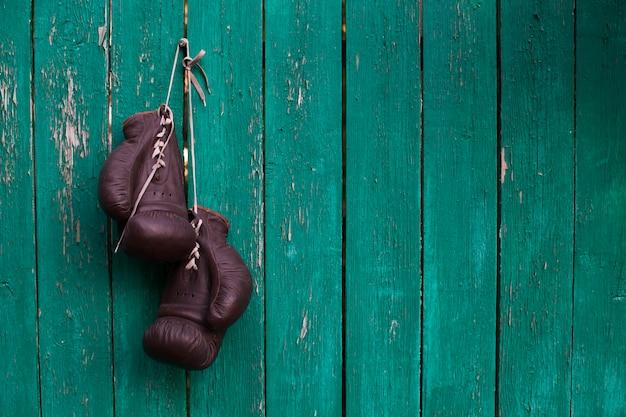 Боксерские перчатки висят на старой деревянной стене Premium Фотографии