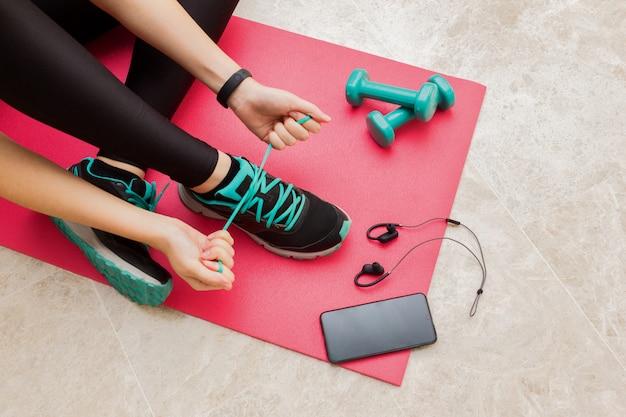 自宅のフィットネスルームで靴ひもを結ぶ若い女性 Premium写真