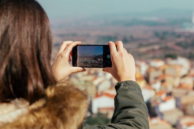 若い女性が彼女のスマートフォンで写真を撮る Premium写真