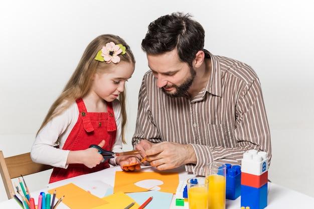 紙のアプリケーションを切り開く娘と父親 無料写真