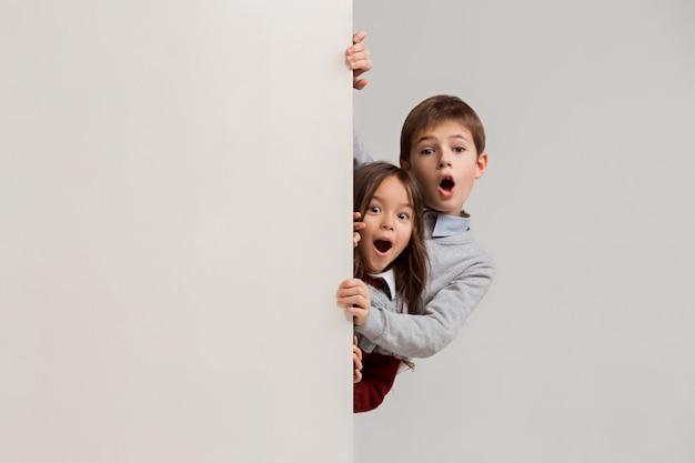端を覗く驚いた子供たちのバナー 無料写真