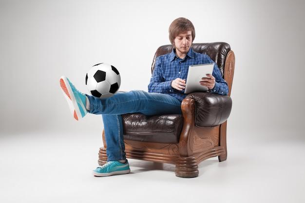 Портрет молодого человека с ноутбуком и футбольный мяч Бесплатные Фотографии