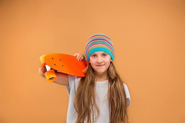 スケートボードを持ってかなりスケーターの女の子 無料写真