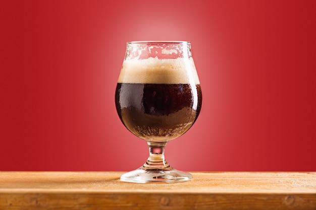 古い木製のテーブルに冷たい泡状の黒ビールのグラス 無料写真