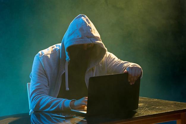 フード付きのコンピューターハッカーがラップトップで情報を盗む 無料写真