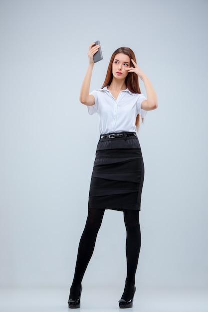 Молодая бизнес-леди на серой стене Бесплатные Фотографии
