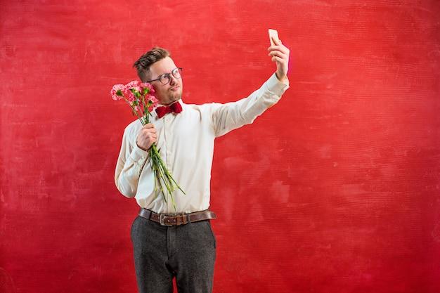 Молодой красивый мужчина с цветами и телефоном Бесплатные Фотографии