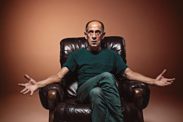 Взволнованный зрелый человек сидит Бесплатные Фотографии