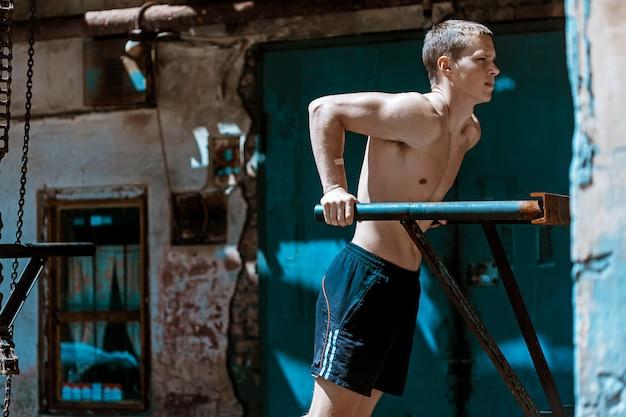 筋肉質の男が鉄の鎖に対してプッシュアップを行う 無料写真