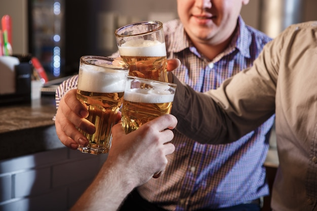 Счастливые друзья пили пиво на прилавке в пабе Бесплатные Фотографии