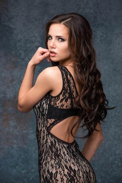 幾何学模様のドレスでポーズをとる彼女の髪を持つ美しい若いブルネットの女性。 無料写真