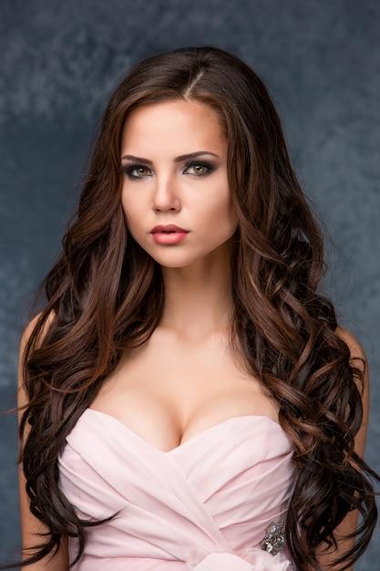 ピンクのドレスでポーズをとる彼女の髪を持つ美しい若いブルネットの女性。 無料写真