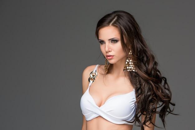 白いビキニでポーズをとる彼女の髪を持つセクシーな若いブルネットの女性。 無料写真