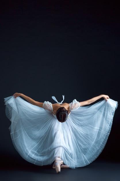 黒い壁に白いドレスのクラシックバレリーナの肖像画 無料写真