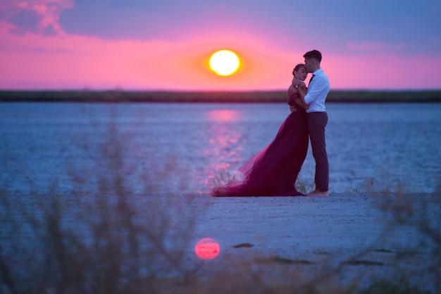 Молодая пара романтический отдых на пляже, наблюдая закат Бесплатные Фотографии